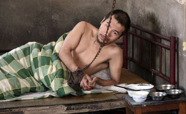 Under lock and key: Hong Chunlin, 37, spends most of his time shackled by his right wrist and lying in bed