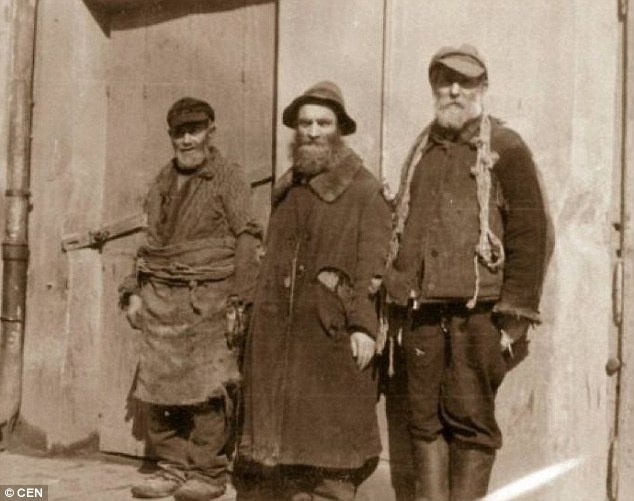 Three elderly men are seen standing against a wall in Lublin Ghetto. Lublin once housed 34,000 Jews - just 230 survived Nazi occupation