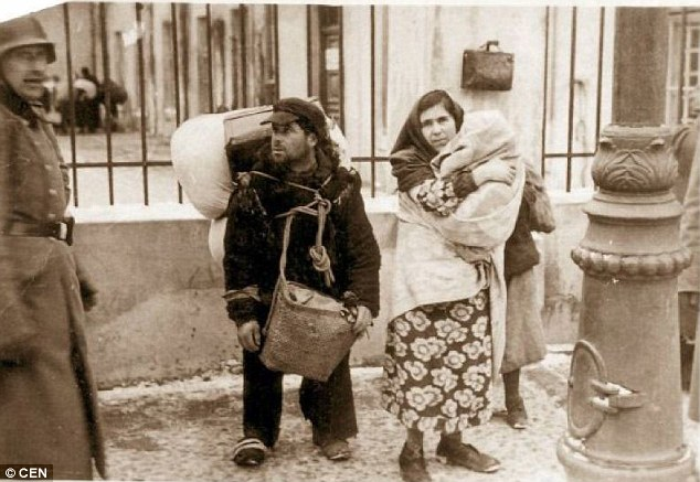 Death camps: A woman holds a child close to her chest alongside a man laden down with belongings as German troops herded residents into cattle trucks to deliver them to their deaths at Belzec