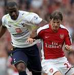 Andrey Arshavin of Arsenal is challenged by Sebastien Bassong of Tottenham Hotspur
