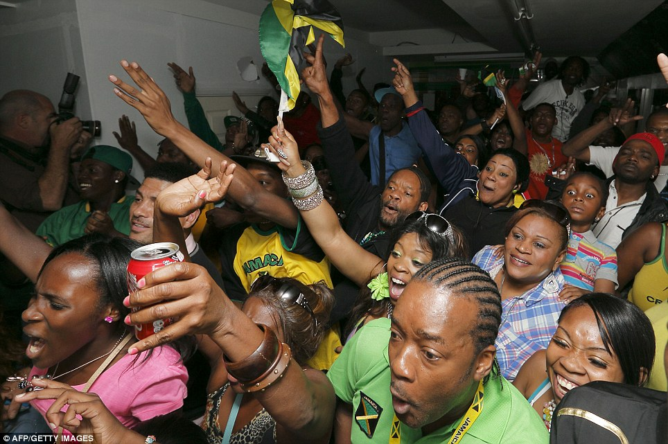 Bolt's our boy: Fans in Brixton watch Usain storm to victory in the 100m