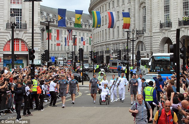 Pride: Britain's greatest Paralympian Tanni Grey-Thompson (centre) leads a team of torchbearers at Piccadilly Circus