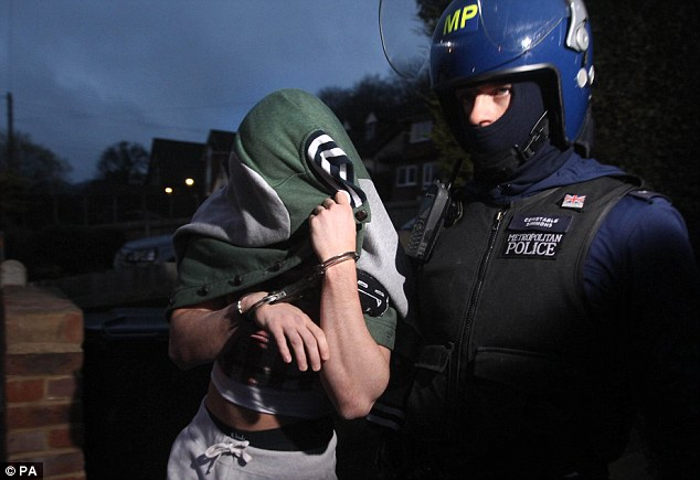 Something to hide? Police make an arrest during an early morning raid after violence at Wembley