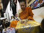 Buddhist monk Phra Prommangkalachan writes blessings on a holy cloth with Leicester City's logo at his temple in Bangkok, Thailand April 18, 2016. REUTERS/Jorge Silva