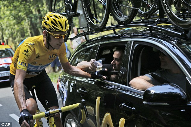 Champagne moment: Wiggins takes a drink of bubbly from his team car during the final stage
