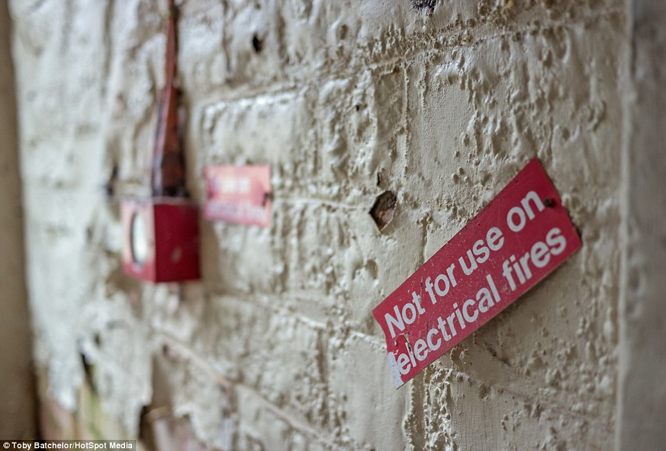 Peeling and chipped walls still bear warnings of health and safety, though an emergency fire alarm is blackened by rot and mould