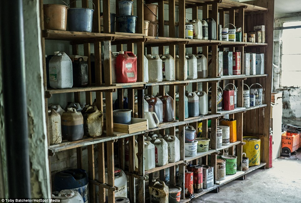 Plastic canisters of petrol and fuel stand untouched alongside paint buckets on a rickety shelving unit in the building which is thought to have been empty for three years