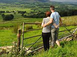 BP384D A young couple look across to the Bowland Fells from Jeffery Hill on Longridge Fell in the Ribble Valley