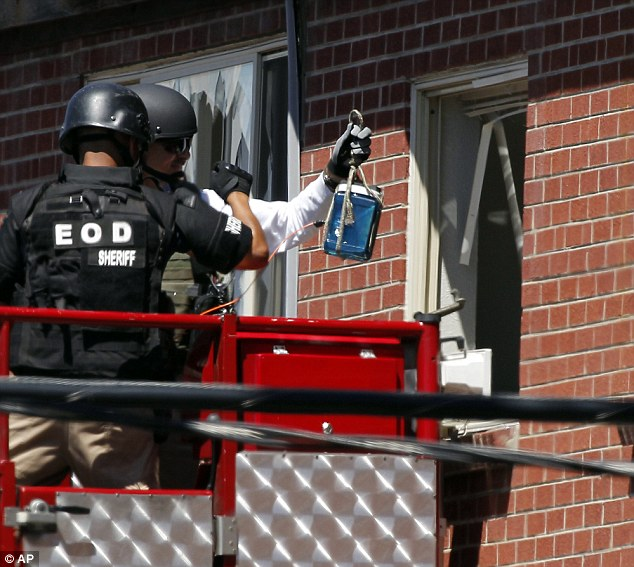 Equipment: Members of law enforcement wearing body armor and helmets prepare what ATF sources describe as a 'water shot' in the apartment of alleged gunman James Holmes Saturday, July 21, 2012 in Aurora, Colo