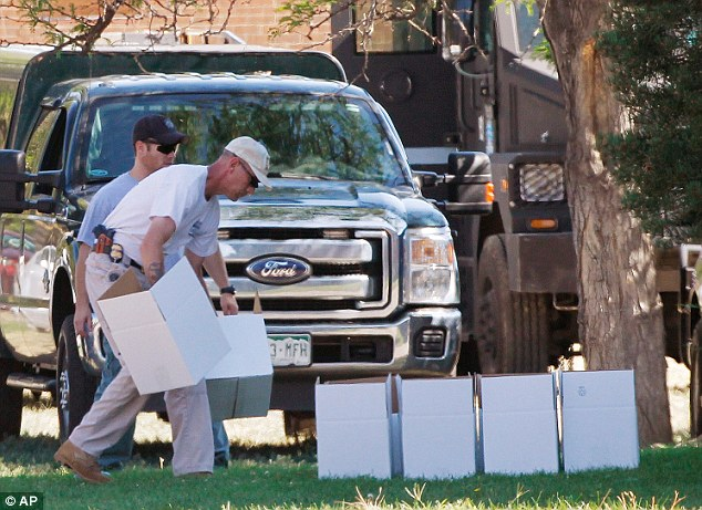 Collection: An ATF agent arranges boxes for evidence in front of the apartment of James Holmes in Aurora, Colo., Saturday, July 21, 2012