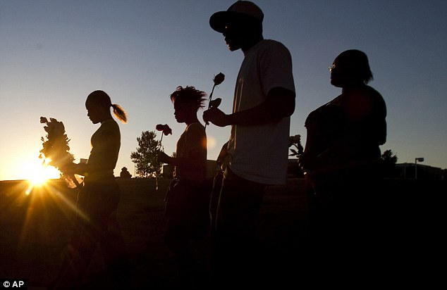 Mourning: From left, Tylecia Amos, 14, Shatyra Amos, 15, Michael Walker, 17, and Mykia Walker, 16, carry flowers to lay at a makeshift memorial across the street from the Century Theater parking lot, on Saturday, July 21, 2012 in Aurora
