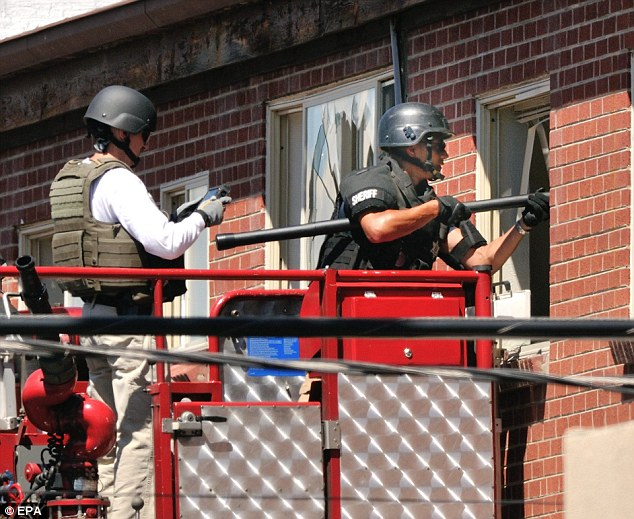 Photographs: Officers use a video camera on a pole to inspect one of the rooms of the apartment of suspected gunman James Holmes in Aurora, Colorado, USA 21 July 2012