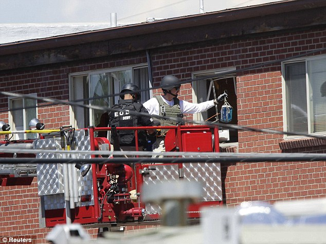 Controlled: Law enforcement officers put a container filled with blue liquid to use in an explosion at the apartment where suspect James Eagan Holmes lived in Aurora, Colorado July 21, 2012