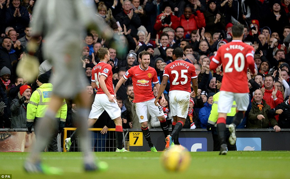A delighted Mata awaits his congratulations from team-mates after his controversial goal
