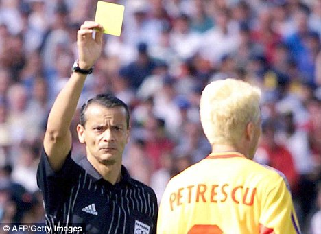 Argentinian referee Javier Alberto Castrilli holds up a yellow card for Romanian defender Dan Petrescu