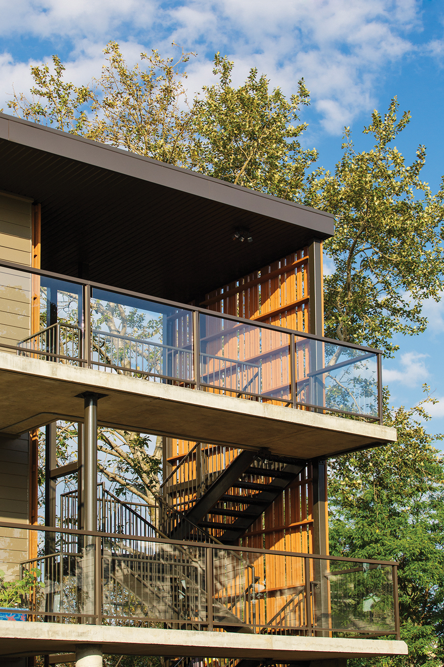 A sheltered, open-air stairway provides access to the individual housing units.