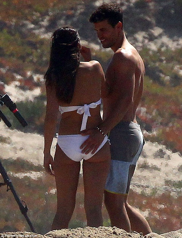 Getting cheeky! Andi Dorfman showed off her svelte shape in a white crochet bikini as one of her suitors touched her firm derriere during the filming of The Bachelorette in Ventura Beach, California on Saturday