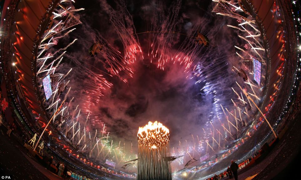 Show of light: Fireworks lit up the sky as the Olympic cauldron burns brightly in the stadium
