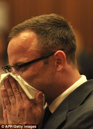 South African Paralympic athlete Oscar Pistorius wipes some tears as he sits in the dock
