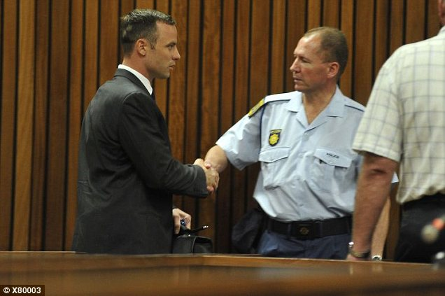Pistorius greets a policeman as he makes his way to the dock.Pistorius has said he shot his girlfriend by mistake through a locked toilet door, thinking that she was an intruder in his home