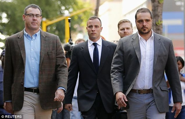 Olympic and Paralympic track star Oscar Pistorius (C) arrives ahead of his trial for the murder of his girlfriend Reeva Steenkamp, at the North Gauteng High Court in Pretoria, March 24, 2014. Pistorius is on trial for murdering his girlfriend Reeva Steenkamp at his suburban Pretoria home on Valentine's Day last year. He says he mistook her for an intruder. REUTERS/Siphiwe Sibeko (SOUTH AFRICA - Tags: SPORT ATHLETICS CRIME LAW)