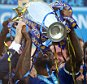 LEICESTER, ENGLAND - MAY 07:  Wes Morgan of Leicester City lifts the Premier League Trophy as his team-mates celebrate becoming Premier League Champions for the 2015/16 Season at the end of the Barclays Premier League match between Leicester City and Everton at The King Power Stadium on May 7, 2016 in Leicester, United Kingdom.  (Photo by Matthew Ashton - AMA/Getty Images)