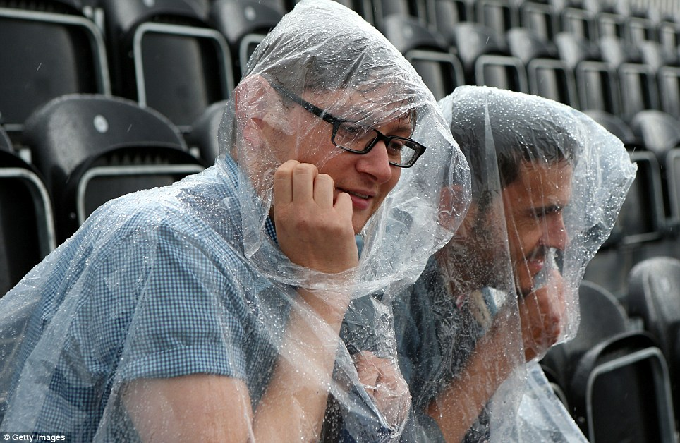 Damp: Equestrian fans shield themselves from the rain at Greenwich Park on day two of the London 2012 Olympic Games