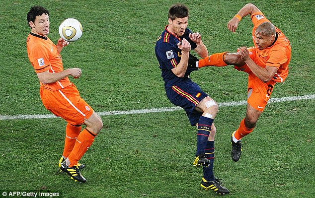 Unfinished business: Alonso (centre) was kicked by Holland's Nigel de Jong (right) in the 2010 final