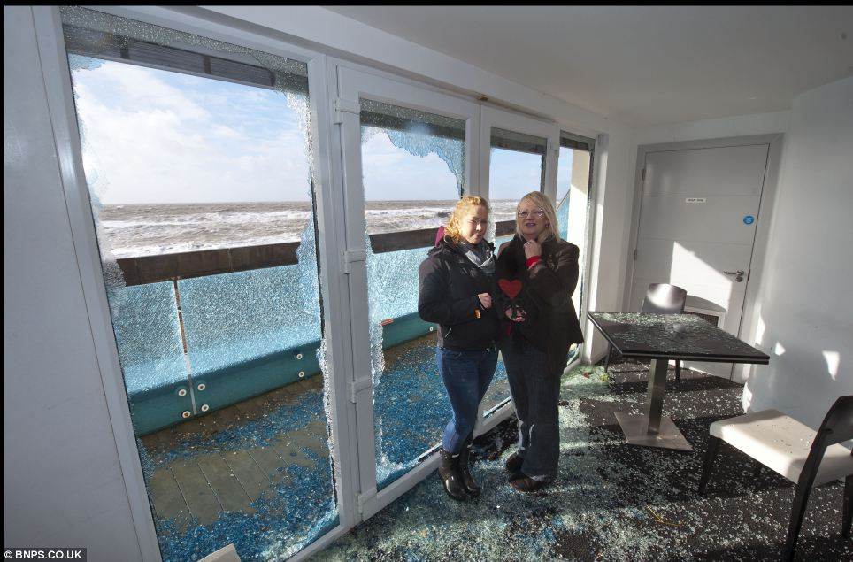 Owner Susan Thompson and daughter Kimberly survey the aftermath of the storm that hit their restaurant last night
