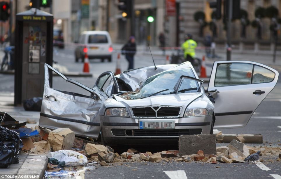 A woman died after part of a building collapsed onto the car she was in on High Holborn, London, during last night's storms