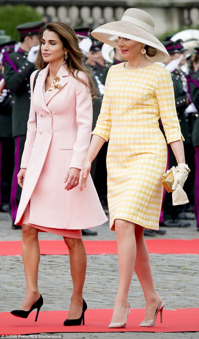 Queen Mathilde royal teamed her striking head gear with a yellow and white houndstooth dress and rose gold satin slingbacks
