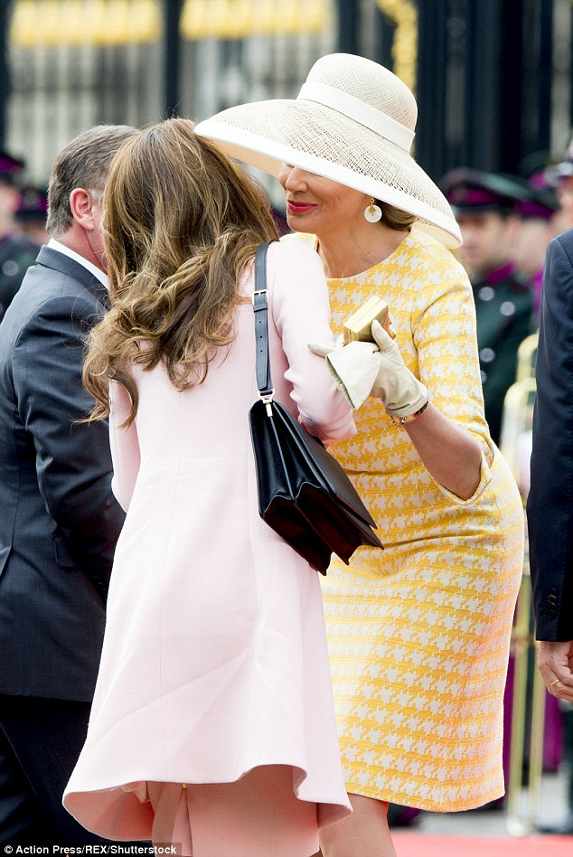 Queen Mathilde may have regretted her choice of a straw hat with an extra wide brim as it caused some technical difficulties when she leaned in to greet her fellow royal with a kiss