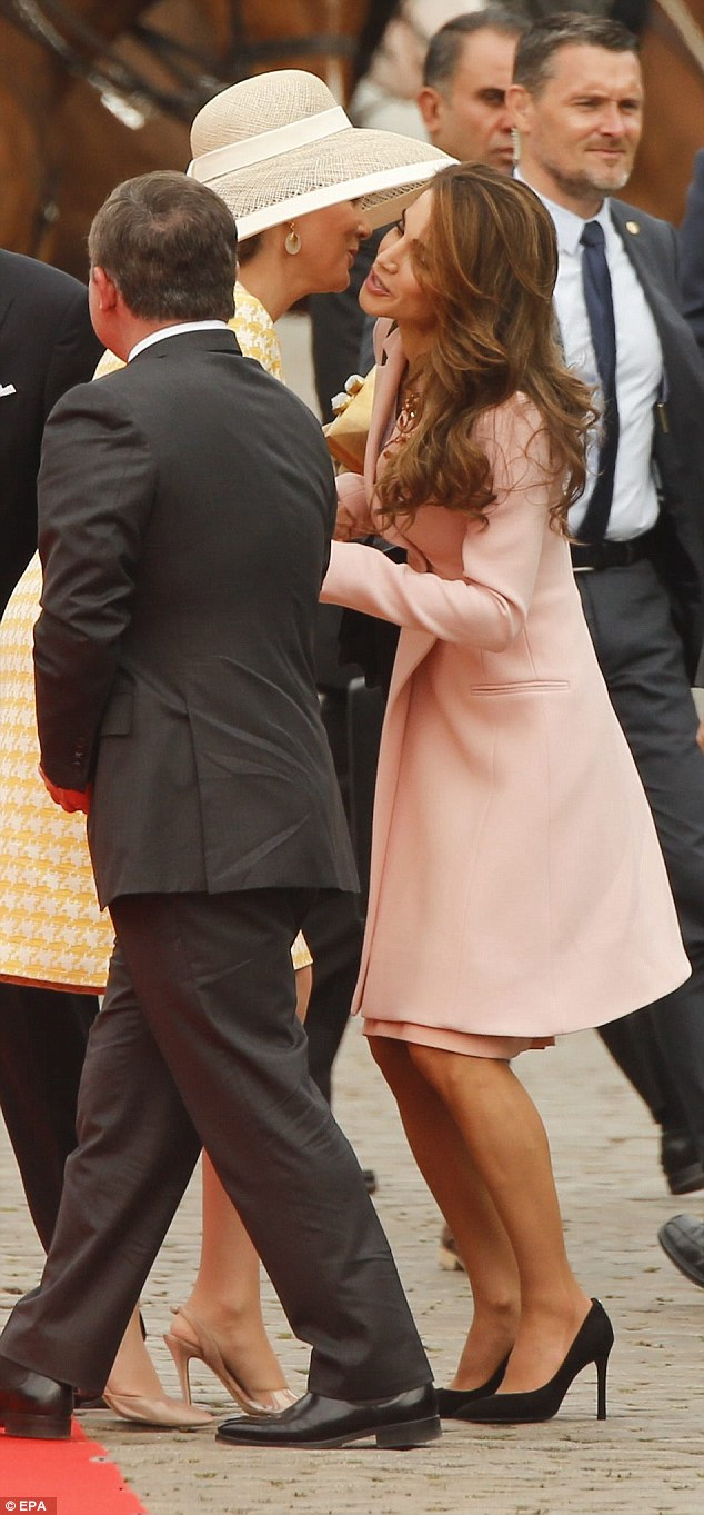 Queen Mathilde leaned in to deliver a kiss on the cheek while Rania ducked and tilted her head to one wide, as her fellow royal's wide-brimmed hat came between them