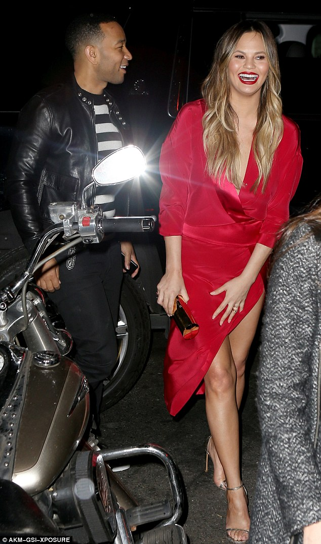 Lady in red: The 30-year-old model wore bright red lip color and a smile as bright as her dress for her dinner date with husband John legend, 37