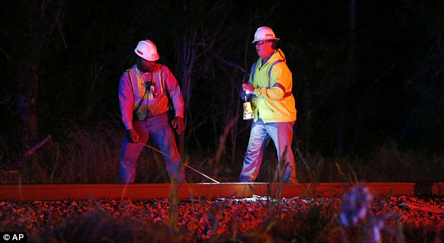 Railroad officials inspect the train track for damage after the Chicago-bound train collided with a pickup truck