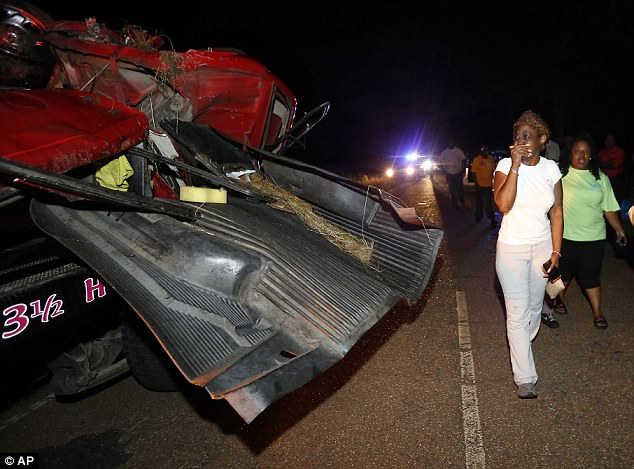 A woman walks past the mangled wreckage of the truck after the accident in Flora, Mississippi