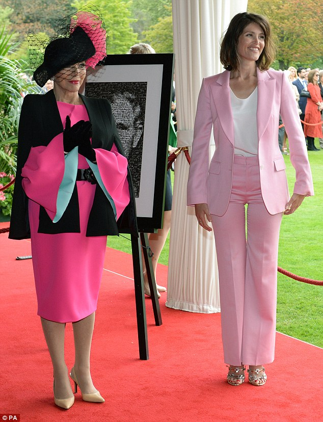 Pretty in pink: Joan donned a bright pink dress, black cape, and statement hat as she joined actress Gemma Arterton at a garden party at Buckingham Palace earlier this week