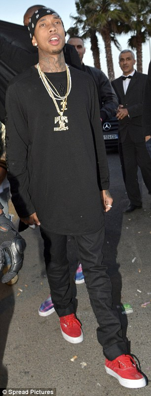 Covering up: Tyga looked to be hiding his Kylie tattoo as he sported a long-sleeved, black T-shirt to party in Cannes on Thursday