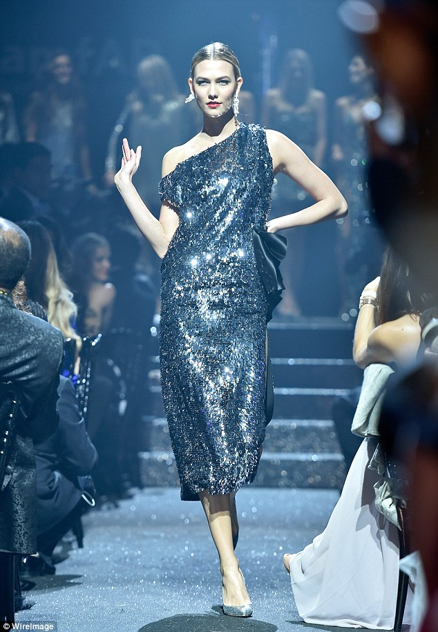 So much sass: Karlie Kloss walked in a heavily sequinned blue gown that was brandished with a theatrical bow at the waist