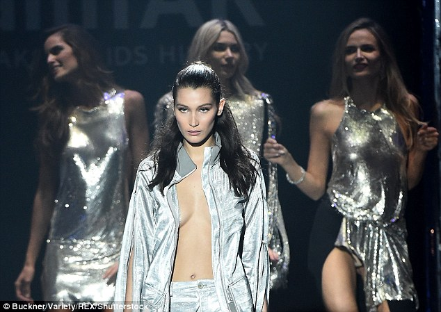 Metallic magic: The 19-year-old stunner put her ample assets almost on full display as she glided down the catwalk completely topless as part of the event's fashion auction, which was inspired by all things disco