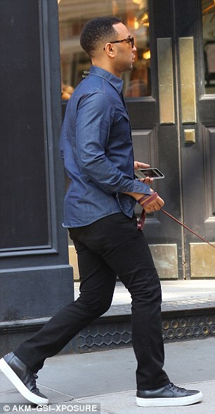 Getting some exercise: The musician checked his phone as he walked the pup wearing a long-sleeved blue shirt with black pants and trainers