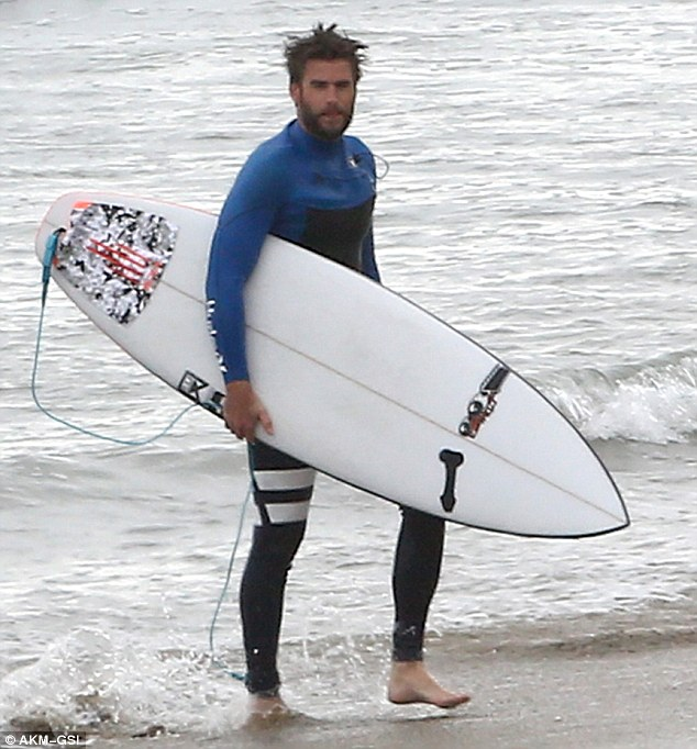 On the beach: Liam carried his white surfboard after his surfing session