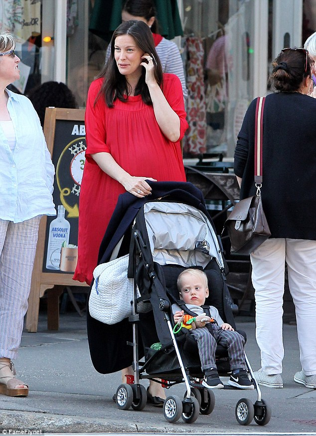 Easy breezy: For their day out, the star went for an easy to wear - and tummy accommodating - loose-fit red dress which she wore with ballet flats