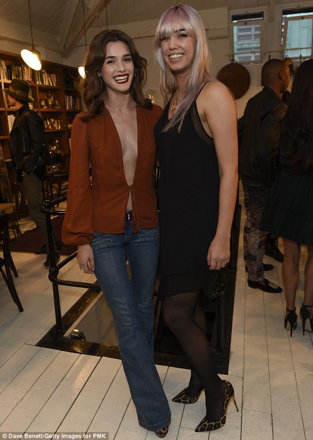 All smiles: Amber, 26, opted for a more somber choice of palette in a little black sheer slip dress with the handkerchief hemline made the most of her toned legs - pictured with actress Sai Bennett