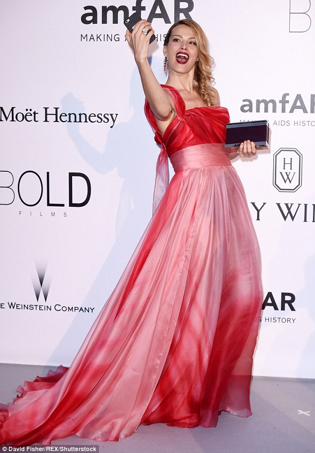 But first...: Not quite done with her entertaining display, Petra striked quite the jovial display as she took selfies while on the red carpet for the fundraiser to help support the global fight to end AIDS