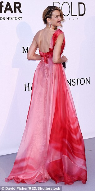 Easy on the eye: The one-shoulder garment boasted different shades of pink ranging from cherry, which highlighted her bustier region and the ends of her dress- to rose ombre, which cinched in her tiny waist