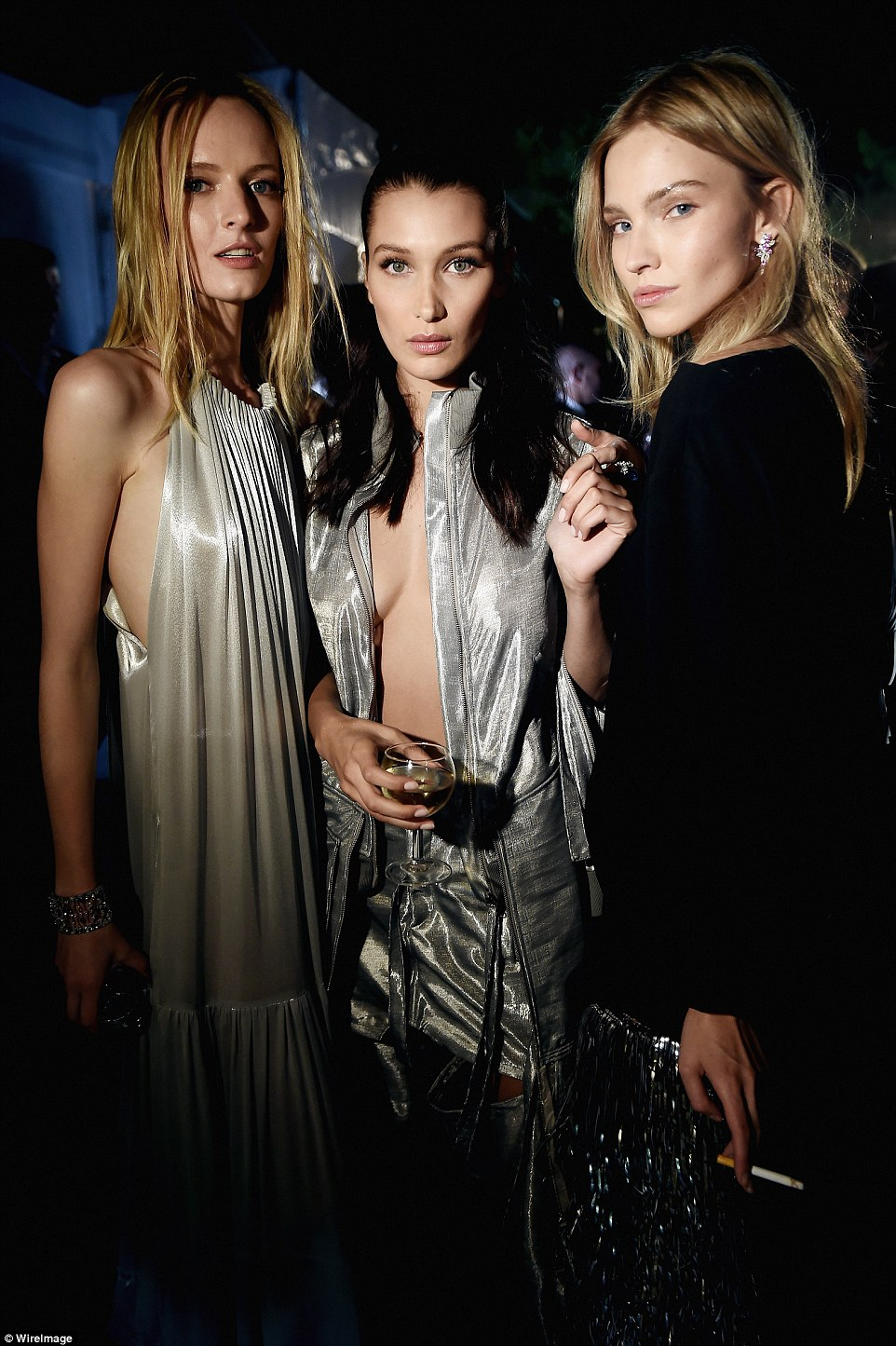 Smoking! Sasha Luss (right) held a cigarette in her hand as she stood with a scantily-clad Bella