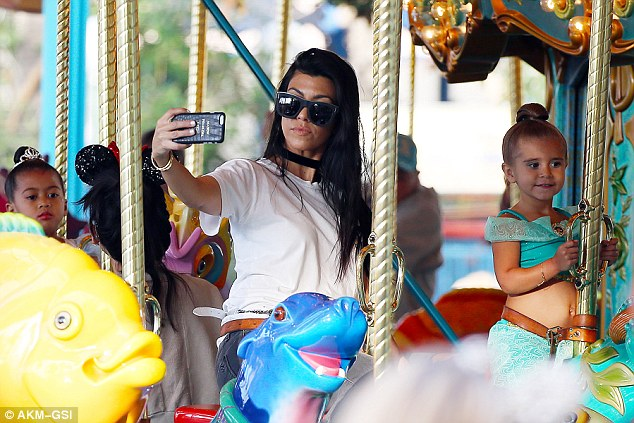 Can't help it:Kourtney Kardashian snapped selfies as she rode a carousel at Disneyland in California with her kids Mason and Penelope on Thursday