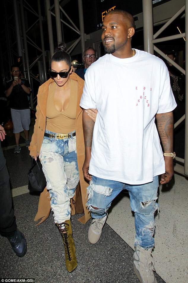 Couple on the move: Kim Kardashian hung onto Kanye West's arm as the couple arrived to catch a flight at Los Angeles International Airport on Thursday night