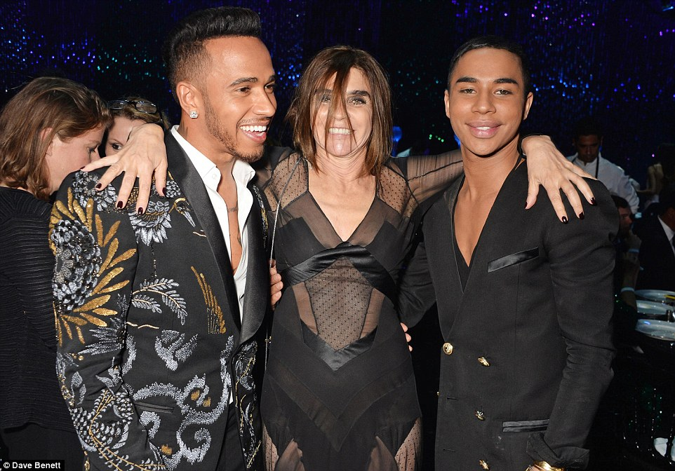 Having a laugh: Carine looked more than happy to be surrounded by the young hunky gents